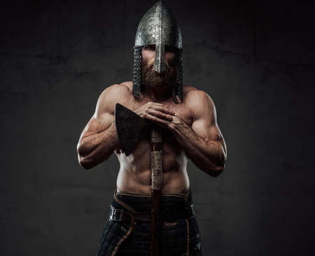 Nude and warlike viking marauder with beard and helmet posing with his two handed axe in dark background. Stock fotó