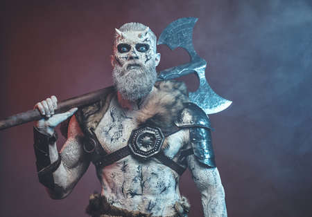 Nordic and mystical fashion undead dressed in dark armour with white hairs and skin holding two handed axe on his shoulder.