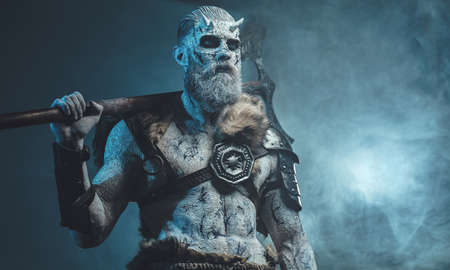 Atmospheric fashion of northern warlike undead in armour with fur with pale skin and white hairs holding axe on his shoulder.