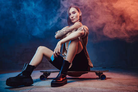 Brown haired beautiful girl with tattoo and smartphone poses in smokey background sitting on skateboard. Banque d'images