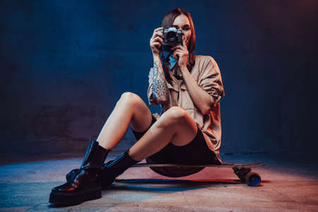 Sportive and stylish girl dressed in casual clothing with short haircut and tattoo sits on skateboard with camera in studio room.
