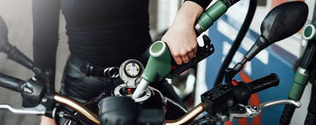 Females gentle hand is holding a fueling gun. Motorcycles tank is fueling by female owner.