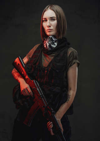 Weared with dark protective clothing female mercenary with short haircut and tattooed hand holding ak74 rifle in dark background. Imagens