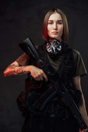 Armed with ak74 rifle female soldier of special forces dressed in dark protective clothing poses in dark background.