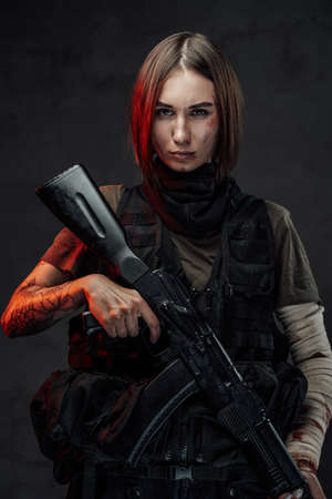 Dreseed in dark armour military woman with short haircut holds rifle with tattooed and bandaged hands in dark background. Imagens