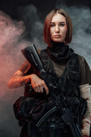 Seductive and tattooed woman dressed in modern and military body armour holding assault rifle in dark foggy background.