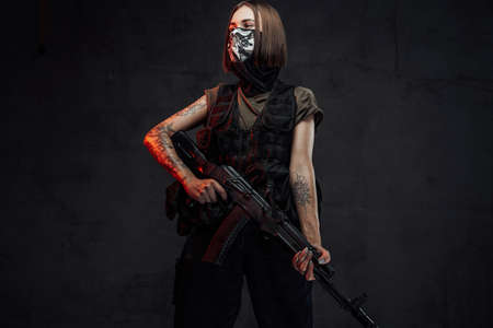 Dressed in dark armour and shirt female soldier with short haircut and weared with mask poses holding ak74 rifle.