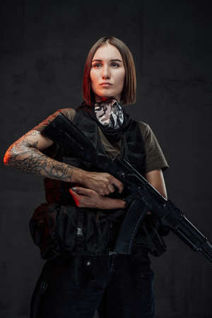 Stylish and martial woman with short haircut and tattooed arm poses holding ak74 rifle in dark background.