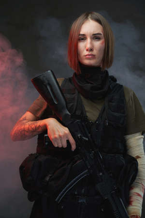 Atmospheric portrait of military woman which dressed in armour with bandaged arm and short haircut holding rifle in smokey background. Stock fotó