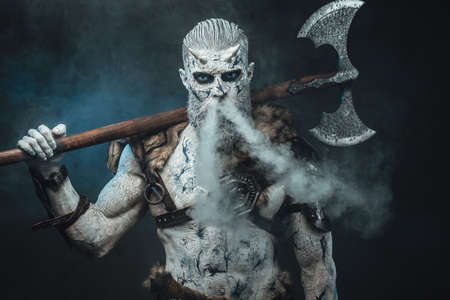 Risen from the dead northern warrior in smokey background with huge two handed axe on his shoulders staring at camera.