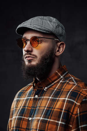 Elegence at the same time brutal hipster in shirt weared with cap and sunglasses poses in dark background.