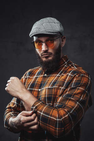 Manly and bearded hipster guy dressed in shirt with cap and weared with sunglasses in dark background.