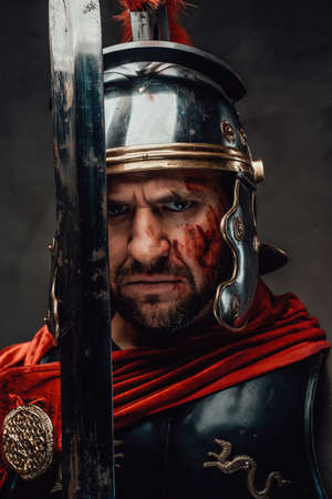 Serious and angry roman soldier dressed in dark armour with helmet and red mantle posing looking at camera and holding a sword. Foto de archivo