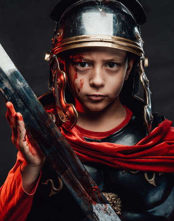 Roman kid fighter dressed in dark armour with red cloak poses looking at camera and holding a sword in dark background.