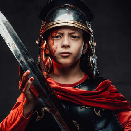 Portrait of serious and combat little legionary with bloody arm and face holding a sword in dark background.