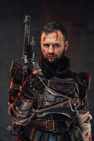 Holding pistol apocalyptic survivor in dark ragged armour and with damaged arm poses in dark background. Banque d'images