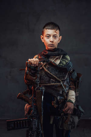 Little apocalyptic kid dressed in ragged clothing with blood on his face poses in dark background holding shotgun.