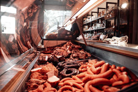 A counter full filled with row of quality raw and smoked in modern and styled butchers shop.