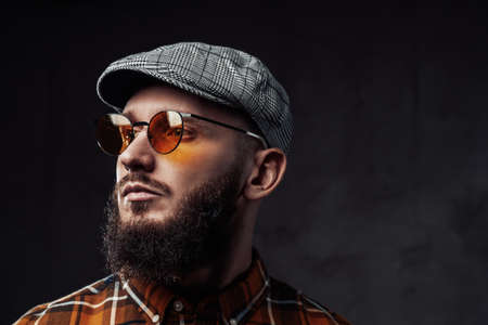 Headshot of adult stylish guy weared with sunglasses and cap with black beard in dark background.