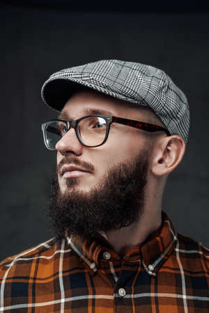 Portrait of stylish and brutal guy with glasses and beard weared with cap he looks away in dark background. Фото со стока