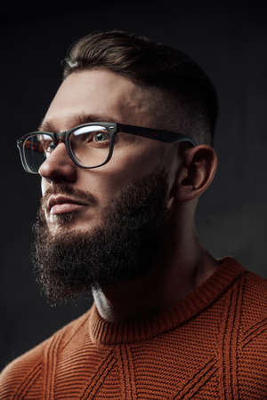 Bearded hipster with stylish hairstyle weared with glasses posing in dark background.