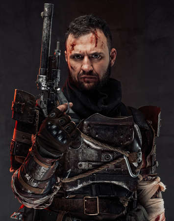 Dressed in ragged dark armour and holding custom pistol survival poses in dark background looking at camera.