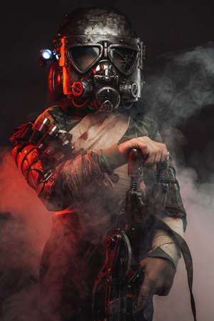 Protected with gas mask and dressed in rags little apocalyptic survivor stays in smokey background holding a gun.