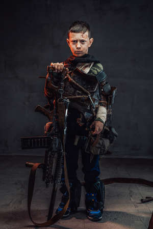 Armoured little apocalyptic kid with blood on his face and short haircut in dark background with shotgun.