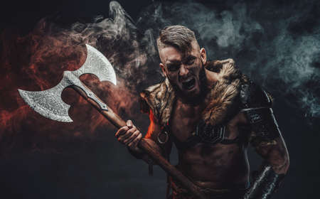 Armed with two handed axe savage and screaming viking in fur with armour in dark background with smoke.