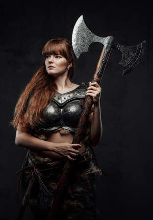 Dressed in dark armour female scandinavian barbarian with brown hairs holding two handed axe in dark background.