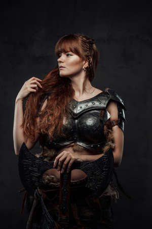 Beautiful but dangerous warlike woman viking with long brown hairs in dark armour holding huge axe in dark background.