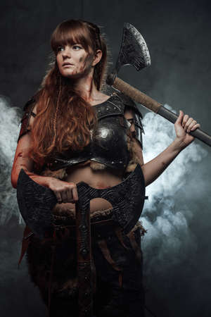Armoured scandinavian lady with long brown hairs holding two huge axes in atmospheric smokey background.