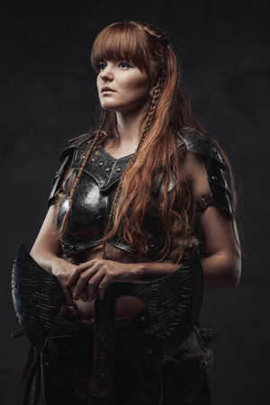 Portrait of pretty and at the same time dangerous nordic female fighter holding huge axe in dark background.
