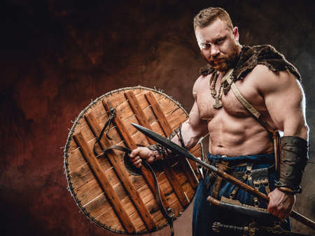 Nordic warlike barbarian with muscular build and torso holding shield and spear in dark background.