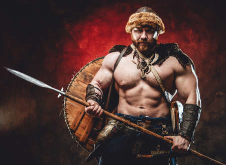 Armed with spear muscular and shirtless scandinavian barbarian with shield on his back poses in dark red background looking at camera.