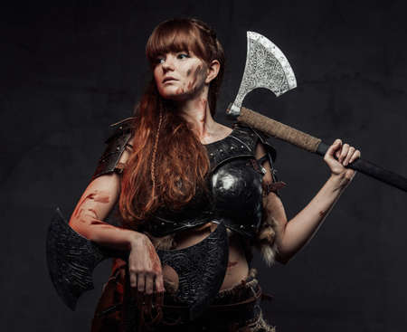 Mighty northern woman warrior in light armour with brown hairs poses in dark background with two huge axes. Reklamní fotografie