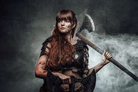 Barbaric female viking in light armour with brown hairs poses in dark smokey background holding two axes. Reklamní fotografie