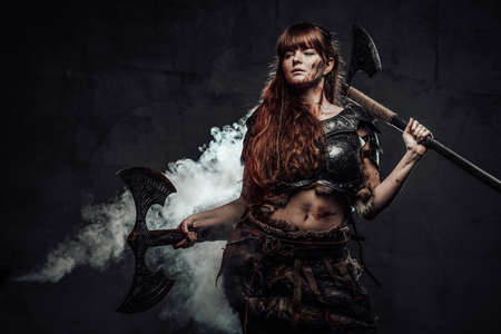 Portrait of beautiful and at the same time dangerous scandinavian woman fighter wielding two axes in dark smokey background.