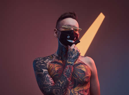 Individual and tattooed macho weared with sunglasses and protective mask poses in dark studio room with spotlight and colourful walls.