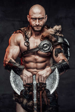 Armed with huge double axe dangerous and hairless viking barbarian in lights armour with fur poses looking at camera with serious bearded face. Reklamní fotografie