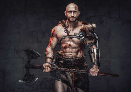 Portrait of a strong and hairless scandinavian seafarer with naked torso and muscular grimy build holding a two handed axe posing in dark background. Reklamní fotografie