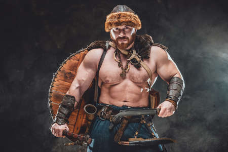 Portrait of shirtless muscular viking with shield on his back and armed with hatchet and knife he poses on dark foggy background.