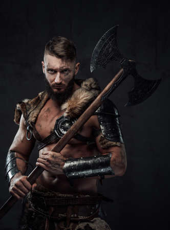 Holding two handed axe on his shoulder scandinavian barbarian in light armour with fur poses in dark background looking at camera.
