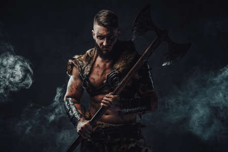 Portrait of evil nordic pagan in light armour with fur staring at camera and holding two handed axe in dark and foggy background.