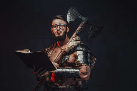 Sad nordic warrior in light armour with fur with eyeglasses and book holding huge axe on his shoulder in dark background. Reklamní fotografie