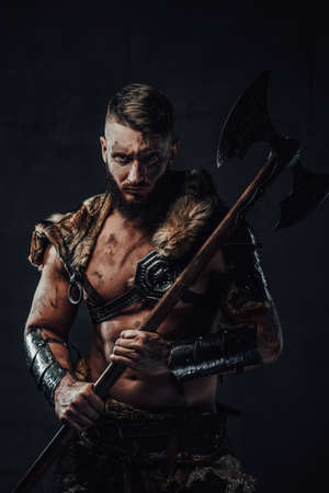 Dressed in dark armour with fur dirty and awesome viking fighter with two handed axe on his shoulder poses in dark background.