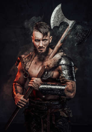 Muscular and awesome viking fighter armed with huge axe and dressed in light armour poses in smokey dark background. Reklamní fotografie