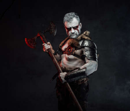 Artistic portrait of a mythical warrior with painted skin in light armour with fur posing in dark background with huge axe.