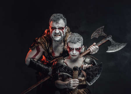 Warlike family a savage father and his son with painted in white skin armed with axes in dark background. Stock fotó