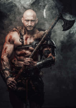 Portrait of a nordic bald warrior armed with two handed axe and in dark armou in atmospheric dark background with smoke looking at camera